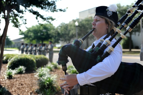 Elizabeth Doss, bagpipe player, plays taps during the 81st Security Forces Squadron Retreat Ceremony May 19, 2016, Keesler Air Force Base, Miss. The ceremony was held during National Police Week, which recognizes the service of law enforcement men and women who put their lives at risk every day. (U.S. Air Force photo by Kemberly Groue)