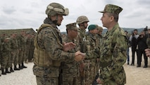 Lt. Gen. Jovica Draganic, Deputy Chief of Staff of the Army of Serbia,(right) presents a coin to Sgt. Ty Heaps, platoon sergeant for 1st platoon, 4th Law Enforcement Battalion, Force Headquarters Group, Marine Forces Reserve, in appreciation of his hard work and efforts during exercise Platinum Wolf 2016 at Peacekeeping Operations Training Center South Base, Bujanovac, Serbia, May 20, 2016. The nations of Bosnia, Bulgaria, Macedonia, Montenegro, Slovenia, Serbia and the United States joined together during the final field exercises to demonstrate their abilities to conduct peacekeeping operations and the ability to work together.