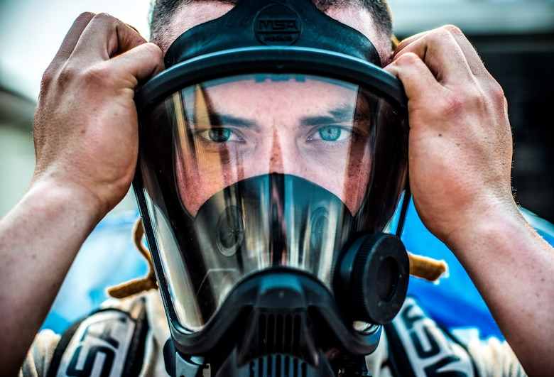 U.S. Air Force Airman 1st Class Petri Brand, a bioenvironmental engineering journeyman with the 35th Aerospace Medicine Squadron, tightens his mask at Misawa Air Base, Japan, May 19, 2016. Brand suited up in a chemical protective suit to show the extent of their work when a chemical is present in the area. Bioenvironmental engineering specialists focus on reducing health hazards in the workplace and the surrounding areas to ensure mission success. (U.S. Air Force photo by Senior Airman Brittany A. Chase)