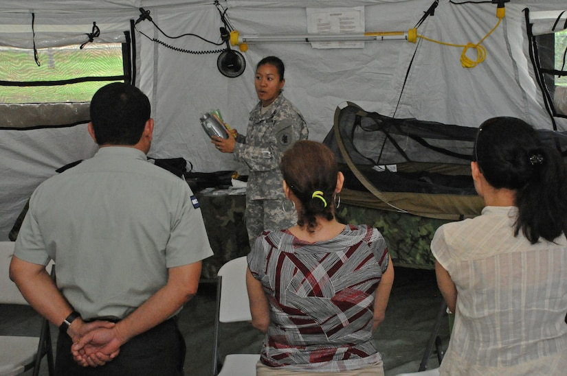 """U.S. Army Maj. Gennelle Lee, U.S. Southern Command Situational Assessment Team operations officer, showcases the contents of an S-SAT """"go-bag"""" to Nicaraguan Civil Defense and U.S. Embassy, Managua, Community Emergency Response Team members May 17, 2016 in Managua, Nicaragua. The team was invited to demonstrate the disaster response assistance capabilities they can provide to all seven Central American nations. The JTF-Bravo S-SAT is designed to be able to depart Soto Cano Air Base within 18 hours of notification of an approved request for assistance that originates from a partner nation by means of the respective U.S. Embassy and U.S. SOUTHCOM. (U.S. Air Force Photo by Capt. David Liapis)"""