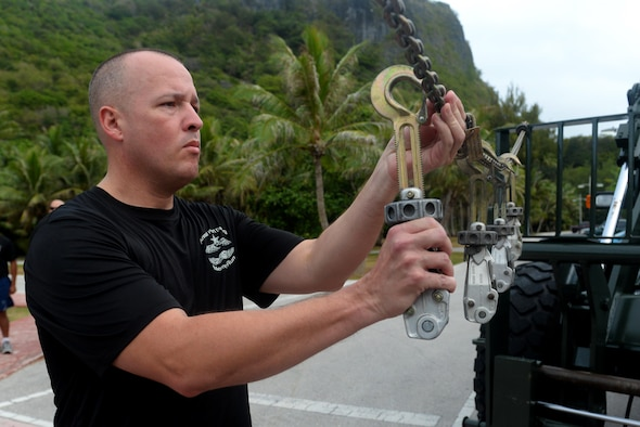 Chief Master Sgt. Travis Owen, 734th Air Mobility Squadron aerial port superintendent, hangs up MB-1 devices on a chain to commemorate fallen air transportation specialists May 20, 2016, at Andersen Air Force Base, Guam. Aerial porters, commonly referred to as Port Dawgs, are responsible for military logistics related to aerial ports and come from multiple units on Andersen to include the 734th AMS, 36th Contingency Response Group and 36th Mission Readiness Squadron. (U.S. Air Force photo by Airman 1st Class Alexa Ann Henderson)