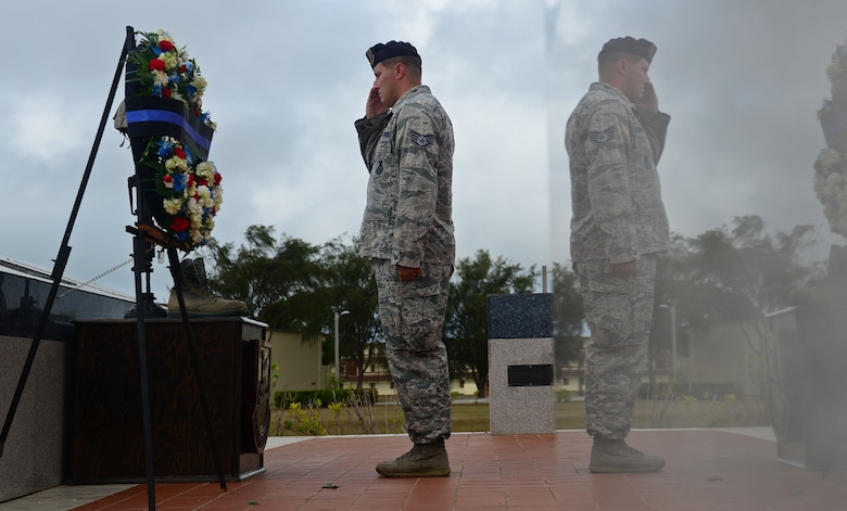 Staff Sgt. Joshua Collins, 36th Security Forces Squadron Emergency Communications Center controller, salutes in front of a symbolic battle cross May 20, 2016, at Andersen Air Force Base, Guam. In honor of Police Week, Airmen paid respect to the fallen with a memorial wreath laying and took turns as vigil guards, similar to the guards at the Tomb of the Unknown Soldier in Arlington, Virginia. (U.S. Air Force photo by Senior Airman Joshua Smoot)