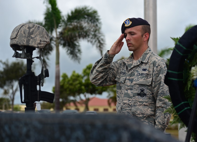 Senior Airman Steven Hendricks, 36th Security Forces Squadron member, salutes a fallen warrior memorial May 20, 2016, at Andersen Air Force Base, Guam. The symbolic battle cross is composed of a replica M4 carbine with a helmet at the top and boots in front. Additionally, 10 dog tags hang from the rifle detailing fallen Airmen and the name of the operation they supported. The vigil was held in honor of fallen security forces members on the occasion of Police Week. (U.S. Air Force photo by Senior Airman Joshua Smoot)