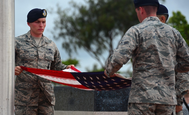 Airmen from the 36th Security Forces Squadron fold the American flag during a retreat ceremony May 20, 2016, at Andersen Air Force Base, Guam. The ceremony was one of several events during Police Week in which Andersen Airmen honored their fallen wingmen. (U.S. Air Force photo by Senior Airman Joshua Smoot)