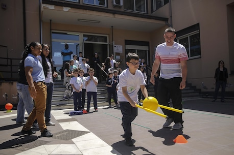 Marines and sailors with Special Purpose Marine-Air Ground Task Force Crisis Response-Africa, watch as children at 3rd Circolo Didattico ''Giovanni Paolo II'' Gravina Di Catania, Italy, run through a circuit course the Marines set up on May 18, 2016.  The Marines and sailors interacted with the children, going over some English for an upcoming test, as well as creating and participating in games during the children's recess period. (U.S. Marine Corps photo by Cpl. Alexander Mitchell/released)