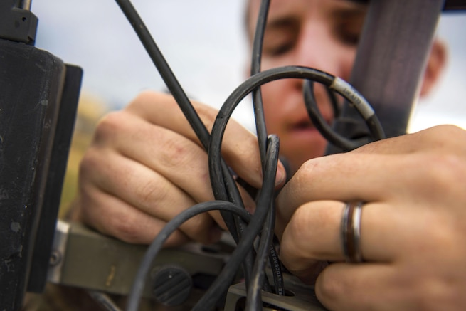 Air Force 1st Lt. Justin D'olimpio connects wires into a meteorological observation system during routine maintenance at Bagram Airfield, Afghanistan, May 16, 2016. D'olimpio is a commander assigned to the 455th Expeditionary Operations Support Squadron. Air Force photo by Senior Airman Justyn M. Freeman