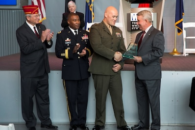 Capt. Samuel L. Baumer (second from right), adjutant for Marine Aircraft Group 41, 4th Marine Aircraft Wing, Marine Forces Reserve, is presented the Mayor's Military Advisory Committee Community Service award by retired Marine Maj. Gen. David M. Mize (right), chairman of the Mayor's Military Advisory Committee, during the Armed Forces Day celebration at the National World War II Museum, May 21, 2016. Baumer was recognized for his outstanding efforts in improving the local community and for setting an excellent example to his fellow Marines. Marine Forces Reserve operates from 160 locations across the U.S. allowing the Marines the unique opportunity to connect with the communities in which they live. (U.S. Marine Corps photo by Lance Cpl. Melissa Martens/ Released)