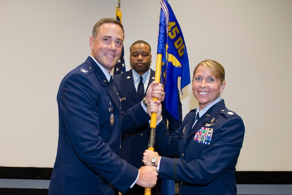 Col. Thomas Falzarano, 45th Operations Group commander, presents Lt. Col. Monique Delauter, 1st Range Operations Squadron commander, with the 1st ROPS guidon during a change of command ceremony May 20, 2016, at the Cape Canaveral Air Force Station Morrell Operations Center, Fla. Changes of command are a military tradition representing the transfer of responsibilities from the presiding officials to the upcoming official. (U.S. Air Force photo/Matthew Jurgens/Released)