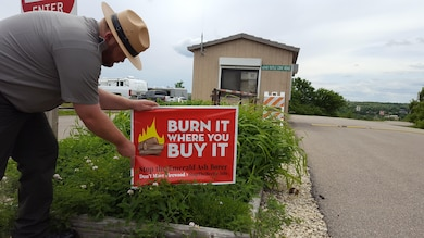 Jeff Austin, Park Ranger with U.S. Army Corps of Engineers Kansas City District at Tuttle Creek Lake places a 'Burn It Where You Buy It - Don't Move Firewood' sign at the entrance to Tuttle Creek Cove Campground in preparation for the upcoming Memorial Day weekend. Natural Resource Managers are asking visitors to leave firewood at home and obtain a supply at or near the area where they intend to burn it. Help us fight invasive species - BUY IT WHERE YOU BURN IT - DON'T MOVE FIREWOOD!