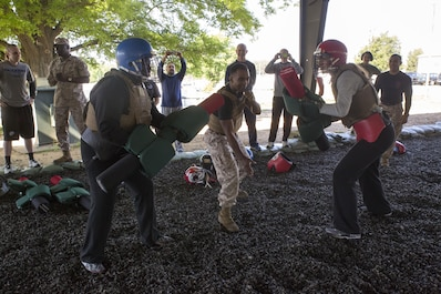 Collegiate coaches train with pugil sticks during the Marine Corps Martial Arts Program iteration of the 2016 Marine Corps Recruiting Command Coaches Workshop at the Martial Arts Center of Excellence aboard Marine Corps Base Quantico, Va., May 20, 2016. Coaches learned how MCMAP fighting skills are used by Marines during close-range encounters with an enemy and how they contribute to the mental and physical development of Marines.