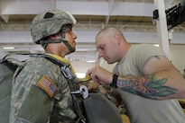 Army Sgt. 1st Class Brandon Ryan, right, inspects Army Spc. Carlos Moscoso's parachute rigging before joint airborne and air transportability training at Joint Base Elmendorf-Richardson, Alaska, May 19, 2016. Ryan, a jumpmaster, and Moscoso are assigned to the 25th Infantry Division's 1st Battalion, 501st Parachute Infantry Regiment, 4th Infantry Brigade Combat Team (Airborne). Air Force photo by Alejandro Pena