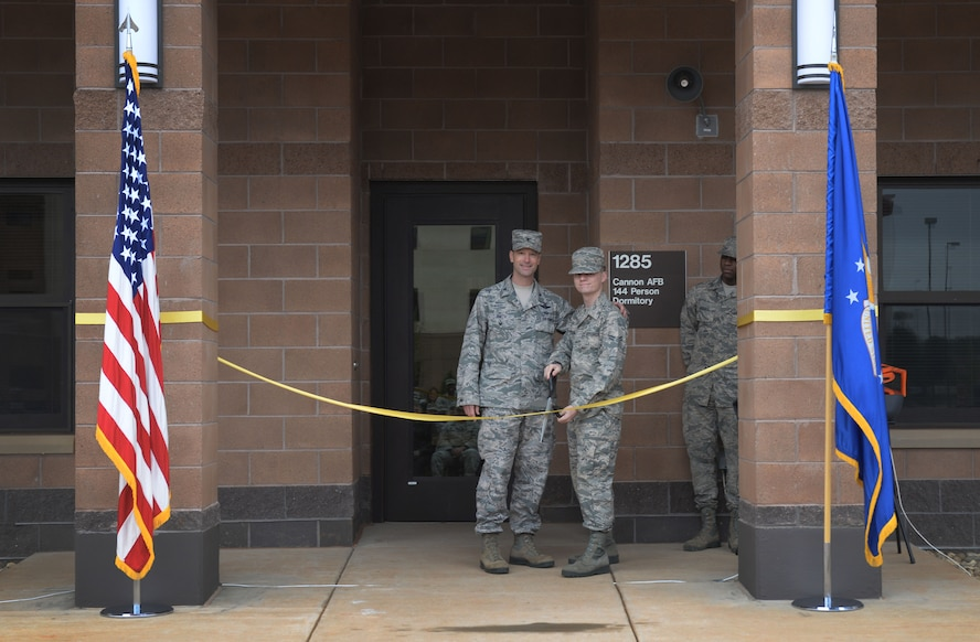 Col. Matthew Smith, 27th Special Operations Wing vice commander, and Airman 1st Class Tyler Nowling, 27th Special Operations Support Squadron air traffic controller, cut the ribbon on a new dorm facility May 18, 2016, at Cannon Air Force Base, N.M. This $20.5 million project began in August 2014 and what completed 175 days prior to the original expected completion date; which is great news for current residents scheduled to occupy the new dorm as this facility will effectively end double-occupancy for the wing. (U.S. Air Force photo/Staff Sgt. Alexx Pons)