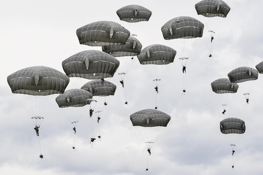 Soldiers descending over Malemute drop zone during airborne training.