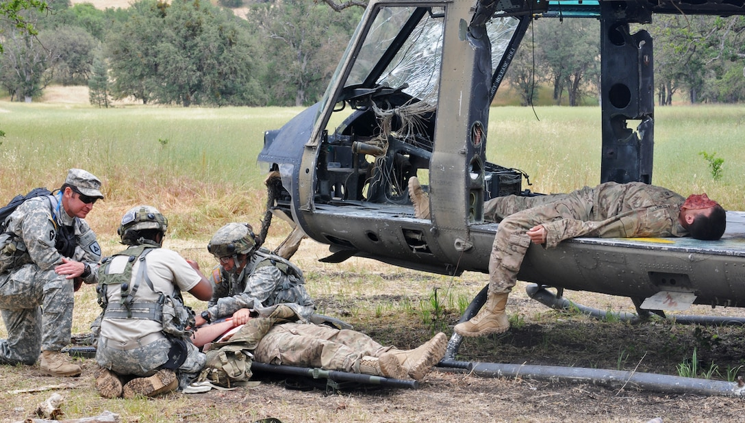 JOLON, Calif. – Sgt. 1st Class James Wardle (right) and Spc. Jacob Duncan (laying left), both Opposing Forces casualties with the 570th Sapper Company, 864th Engineer Battalion, 555th Engineer Brigade of Joint Base Lewis-McChord, Wash., simulate casualties of a helicopter crash during a route-clearance and medical training exercise at Fort Hunter Liggett, Calif., May 6. (U.S. Army photo by Sgt. Kimberly Browne, 350th Public Affairs Detachment)