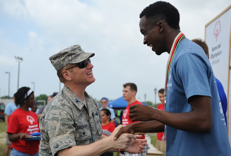 Col. Dennis Scarborough, 81st Training Wing vice commander, congratulates Desmond Brown, Special Olympics athlete, on earning a gold medal in the 50 meter race during the Special Olympics Mississippi Summer Games at the triangle track May 21, 2016, Keesler Air Force Base, Miss. More than 700 athletes and 3,000 volunteers worked together to hold competitions throughout the day. This is the 30th year Keesler has hosted the state Special Olympics.  (U.S. Air Force photo by Kemberly Groue)