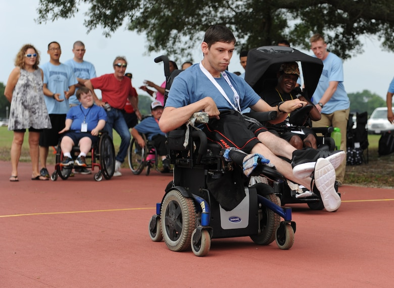 Chris Dillard and Gary Anderson, Special Olympics athletes, participate in the 25 meter motorized wheelchair race during the Special Olympics Mississippi Summer Games at the triangle track May 21, 2016, Keesler Air Force Base, Miss. More than 700 athletes and 3,000 volunteers worked together to hold competitions throughout the day. This is the 30th year Keesler has hosted the state Special Olympics.  (U.S. Air Force photo by Kemberly Groue)