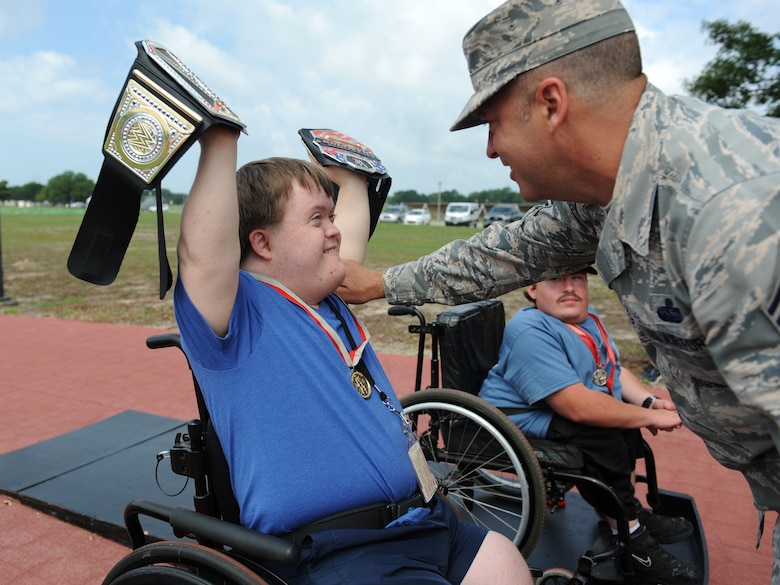 Austin Seymour, Special Olympics athlete, is awarded the gold medal by Chief Master Sgt. Derek Fromenthal, 338th Training Squadron superintendent, for the 25 meter wheelchair race during the Special Olympics Mississippi Summer Games at the triangle track May 21, 2016, Keesler Air Force Base, Miss. More than 700 athletes and 3,000 volunteers worked together to hold competitions throughout the day. This is the 30th year Keesler has hosted the state Special Olympics.  (U.S. Air Force photo by Kemberly Groue)