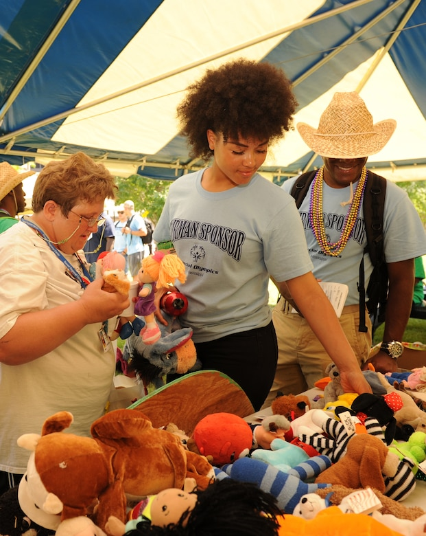 Linda McGriff, Special Olympics athlete, and her Airman sponsors, Airmen Amia Hammett and Ryan Ramjit, 336th Training Squadron students, select stuffed animals at Olympic Village during the Special Olympics Mississippi Summer Games May 21, 2016, Keesler Air Force Base, Miss. More than 700 athletes and 3,000 volunteers worked together to hold competitions throughout the day. This is the 30th year Keesler has hosted the state Special Olympics.  (U.S. Air Force photo by Kemberly Groue)