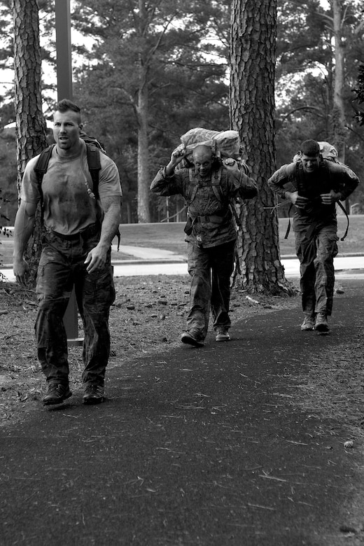 Brent Gilley (left), husband of Staff Sgt. Nicole Gilley, 4th Security Forces Squadron military working dog handler, Master Sgt. Andrew Earll, 4th SFS first sergeant, and Tech. Sgt. Matthew Thomas, 4th SFS NCO in-charge of plans and programs, participate in a ruck march, May 19, 2016, at Seymour Johnson Air Force Base, North Carolina. Participants completed a two-mile ruck march carrying 35 pounds for time during one of the many events held in honor of Police Week. (U.S. Air Force photo by Airman Shawna L. Keyes/Released)