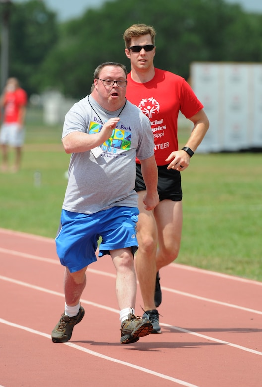 John Toche, Special Olympics athlete, participates in the 100 meter walk with the assistance of Airman 1st Class Joshua Hinson, 335th Training Squadron student, during the Special Olympics Mississippi Summer Games at the triangle track May 21, 2016, Keesler Air Force Base, Miss. More than 700 athletes and 3,000 volunteers worked together to hold competitions throughout the day. This is the 30th year Keesler has hosted the state Special Olympics.  (U.S. Air Force photo by Kemberly Groue)
