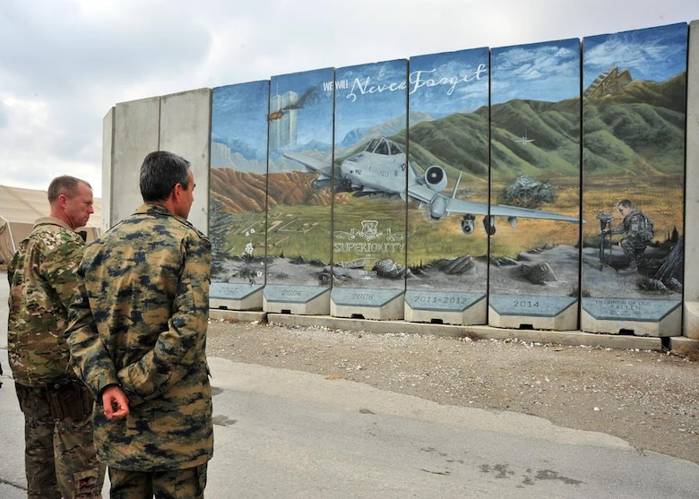 "Two coalition service members admire a mural painted at a deployed location by Staff Sgt. Omar, 432nd Wing sensor operator in training at Creech Air Force Base, Nevada. The painting depicts an A-10 Thunderbolt providing close air support in 2014. On the left, the twin towers burn next to the words, ""we will never forget,"" to symbolize the events of September 11, 2001. On the right, Omar depicted one of his wingmen, an Airman holding a battle cross to commemorate fallen soldiers. (Courtesy Photo)"