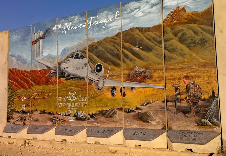 "A mural by Staff Sgt. Omar, 432nd Wing sensor operator in training, depicts an A-10 Thunderbolt providing close air support in 2014, at a deployed location. Omar was previously assigned to the 442nd Fighter Wing at Whiteman Air Force Base, Missouri. On the left, the twin towers burn next to the words, ""we will never forget,"" to symbolize the events of September 11, 2001. On the right, Omar depicted one of his wingmen, an Airman holding a battle cross to commemorate fallen soldiers. (Courtesy Photo)"