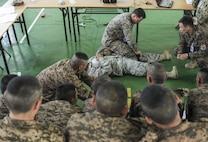 160523-N-WI365-029 ULAANBAATAR, Mongolia (May 23, 2016) - Fleet Marine Force (FMF) Hospital Corpsman 2nd Class Joshua Rogers, assigned to 3rd Medical Battalion and Sergeant Gerald Mina assigned to the Hawaii National Guard, demonstrate how to properly apply a tourniquet to members of the Mongolian Armed Forces during a casualty control familiarization class as part of Khaan Quest 2016. Khaan Quest 2016 is an annual, multinational peacekeeping operations exercise hosted by the Mongolian Armed Forces, co-sponsored by U.S. Pacific Command, and supported by U.S. Army Pacific and U.S. Marine Corps Forces, Pacific. Khaan Quest, in its 14th iteration, is the capstone exercise for this year's Global Peace Operations Initiative program. The exercise focuses on training activities to enhance international interoperability, develop peacekeeping capabilities, build to mil-to-mil relationships, and enhance military readiness.