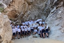 """Airmen from the 944th Force Support Squadron pose for a photo during a hike at White Tank Mountain Regional Park, Ariz. April 29, 2016. A total of 48 Airmen, including two medics, participated in the hike to promote fitness and boost morale. The unit also wanted to take advantage of the 3-day Unit Training Assembly by doing an outdoor team building activity before the """"intense summer heat arrives"""" according to Maj. Sheilia Kane, 944th FSS operations officer. (U.S. Air Force photo by Staff Sgt. Lausanne Kinder)"""