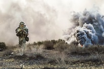 A soldier uses smoke to conceal his movement during Decisive Action Rotation 16-06 at the National Training Center at Fort Irwin, Calif., May 16, 2016. The soldier is assigned to 3rd Infantry Division. Army Photo by Spc. Kyle Edwards
