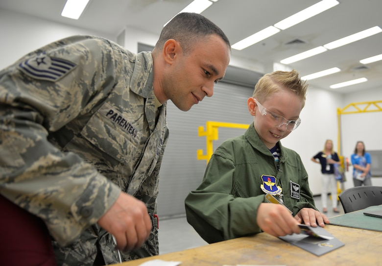 Tech. Sgt. Joseph Parenteau, 33rd Maintenance Squadron non-commissioned officer in charge of low observables, teaches Pilot for a Day, Christian Loafman, how to place lettering on aircraft metals at Eglin Air Force Base, Fla., May 18, 2016. Christian toured the low observable and non-destructive inspection shops where he learned how these Airmen check the aircraft to maintain its ability to fly safely. (U.S. Air Force photo/Senior Airman Andrea Posey)