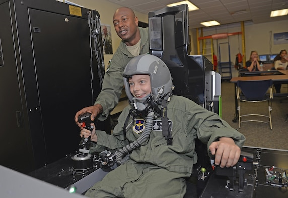 Tech. Sgt. Omar Robinson, 96th Medical Group aerospace and operational physiology technician, teaches Pilot for a Day, Christian Loafman, how to control flight simulator at Eglin Air Force Base, Fla., May 18, 2016. During the visit, Christian was treated like a real F-35A Lightning II pilot and given a flight equipment locker, flight suit and mission brief before he flew a mission using the flight simulator. (U.S. Air Force photo/Senior Airman Andrea Posey)