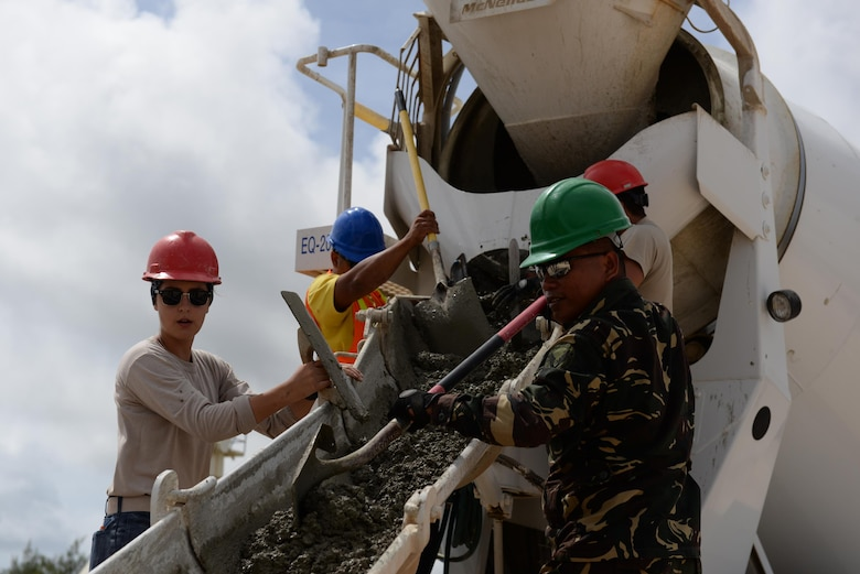 U.S. and Philippine Airmen push concrete from a cement truck during a Pacific Unity tilt-up workshop May 18, 2016, at Andersen Air Force Base, Guam. Pacific Unity events are designed to build partnerships and promote interoperability through the equitable exchange of civil engineer related information. (U.S. Air Force photo by Airman 1st Class Jacob Skovo)