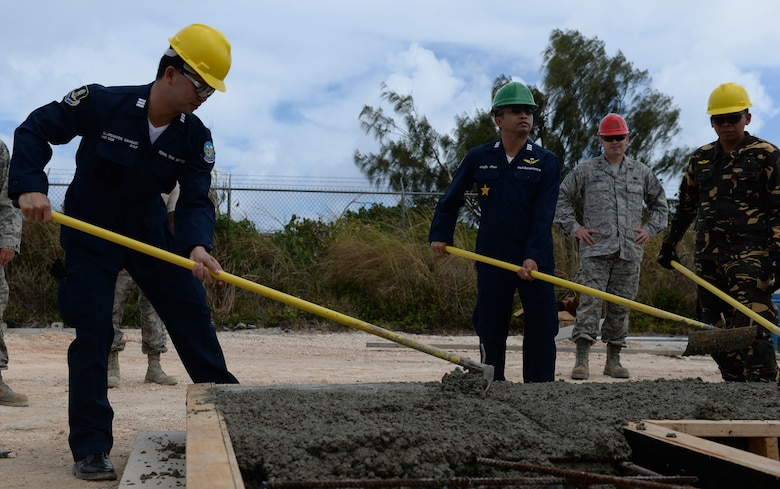 Delegates from the Royal Thai and Philippine air forces spread concrete in a cast to make a wall used for tilt-up construction May 18, 2016, at Andersen Air Force Base, Guam. The Pacific Unity 16-1 tilt-up workshop is a Pacific Air Forces-led engagement focusing on a series of civil engineering subject-matter expert exchanges designed to increase partner capabilities, military relations and regional stability for the Indo-Asia-Pacific region. (U.S. Air Force photo by Airman 1st Class Jacob Skovo)