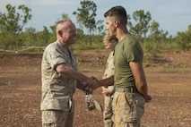 Lt. Gen. Lawrence D. Nicholson, III Marine Expeditionary Force Commanding General, presents a III MEF challenge coin to Cpl. Brett J. Nelson, a bulk fuel specialist with Marine Wing Support Squadron 172, at Mount Bundey Airfield, Northern Territory, Australia, on May 11, 2016. Nelson, from Springfield, Ohio, earned the coin for his outstanding conduct while deployed. Nicholson visited Marines with the Marine Rotational Force – Darwin's Aviation Combat Element at a forward arming and refueling point.