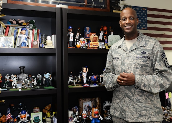 Chief Master Sgt. Michael McMillan, 36th Wing command chief, poses for a photo in front of his sports memorabilia collection Feb. 20, 2016, at Andersen Air Force Base, Guam. As command chief, McMillan's responsibilities are to support the health and welfare of the Airmen of the 36th Wing and to ensure they have everything they need to complete the mission. (U.S. Air Force photo by Senior Airman Cierra Presentado)