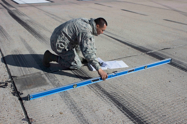 Master Sgt. Robinson Hidalgo, superintendent of the Air Force Civil Engineer Center Airfield Pavement Evaluation, or APE, Team, checks the slope of the runway during a recent evaluation at Hill AFB, Utah.