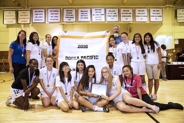 Players and coaches from the Panthers girls' soccer team from Yokota High School, Yokota Air Base, pose with their plaque and banner after winning first place in the Far East Soccer Tournament hosted by Matthew C. Perry High School at Marine Corps Air Station Iwakuni, Japan, May 19, 2016. The Far East Soccer Tournament is the largest soccer event that Department of Defense Education Activity Schools Pacific in mainland Japan, Okinawa, Korea and International Schools have to look forward to compete in all season. (U.S. Marine Corps photo by Lance Cpl. Donato Maffin/Released)