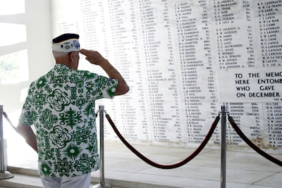 Sterling R. Cale, treasurer, Pearl Harbor Survivors Association Unit 1, saluting his fallen comrades in the rear of the USS Arizona Memorial.