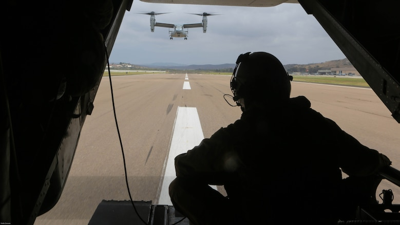 Cpl. Matthew Maenner, crew chief with Marine Medium Tiltrotor Squadron 163 (Reinforced) observes the other MV-22B Osprey returning from Marine Corps Base Camp Pendleton and landing aboard Marine Corps Air Station Miramar, Calif., May 17. Marines with VMM0-163 (Rein.) supported the 11th Marine Expeditionary Unit during a simulated raid and supplied four MV-22B Ospreys, two AH-1W Cobras, two UH-1Y Hueys and one CH-53E Super Stallion.