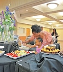Dominique Woods, wife of Sgt. Montanize Woods, 1st Battalion, 5th Field Artillery Regiment, 1st Armored Brigade Combat Team, 1st Infantry Division, helps her daughter Meela Woods, 4, pick fruit from the buffet for Mother's Day brunch May 8 at Riley's Conference Center.  Despite the traditions of mothers getting Mother's Day off or at least the morning, Dominique had her hands full with Meela as she eagerly rushed back to the table to eat her fruit before Dominique could finish with her own selections.