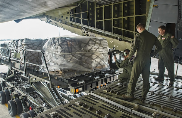 Airmen with the 356th Airlift Squadron direct an Atlas K-loader to an awaiting C-5M Super Galaxy aircraft May 13, 2016 at Joint Base San Antonio-Lackland, Texas. The 433rd Airlift Wing and 502nd Logistics Readiness Squadron worked together to ensure 90,000 pounds of food aid made it to Yoro, Honduras. (U.S. Air Force photo by Benjamin Faske)