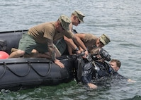 Seabee divers pull Navy Petty Officer 2nd Class Justin Lieder out of the water during an unconscious diver drill at Naval Inactive Ship Maintenance Facility at Pearl Harbor, Hawaii, May18, 2016. The divers are assigned to Underwater Construction Team 2, Construction Dive Detachment Alpha, which provides responsive inshore and underwater construction capabilities. Navy photo by Petty Officer 1st Class Charles E. White