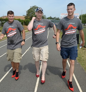 (Left to right) Petty Officer 2nd Class Perry Davis, Petty Officer 2nd Class Kurtis Glenn and Petty Officer 3rd Class Benjamin Rozeboom, Naval Branch Health Clinic-Albany, make their way around the track wearing red high-heeled shoes.  The Sailors participated in the Walk a Mile in Her Shoes event benefitting Lily Pad at Deerfield-Windsor School's Webb Memorial Stadium in Albany, Ga., recently.