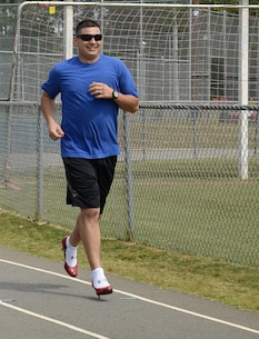 Maj. Frank Sierra, information solution architect, Command, Control, Communications and Computers Department, Marine Corps Logistics Command, runs one of four laps around the track in heels to support the Lily Pad's Walk a Mile in Her Shoes event at Deerfield-Windsor School's Webb Memorial Stadium in Albany, Ga., recently.