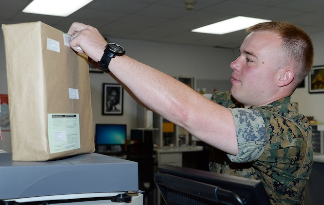 Staff Sgt. Steven McGahee, postal clerk, Marine Corps Logistics Base Albany, labels a package at the installation's mailroom, May 12. McGahee was meritoriously promoted to his current rank recently after winning the final meritorious promotion board at Marine Corps Installations Command.