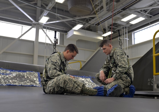 Airman 1st Class Griffin Smith and Airman 1st Class William Manion, 33rd Maintenance Squadron aircraft fuels system repairmen apprentices, gather tools to perform maintenance on an F-35A Lightning II panel at Eglin Air Force Base, Fla., Jan. 13, 2016. Fuel systems Airmen maintain fuel tanks and cells by removing, repairing and replacing malfunctioning components. (U.S. Air Force Photo/Senior Airman Andrea Posey)