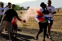 A volunteer throws colored powder at participants during the Cultural Awareness Color Run at Davis-Monthan Air Force Base, Ariz., May 20, 2016. There were more than 90 participants and about 30 volunteers at the run. (U.S. Air Force photo by Airman Nathan H. Barbour/Released)
