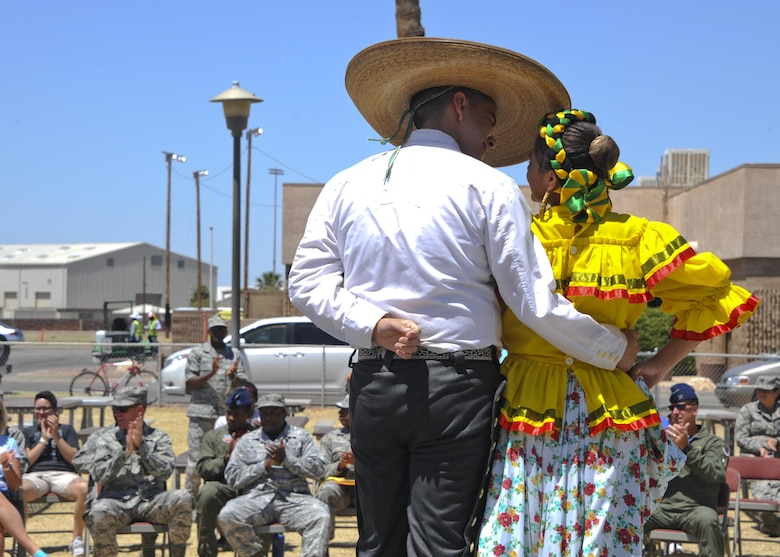 U.S. Airmen and civilians applaud as the Folklorico Dance Performance concludes during the Cultural Awareness Festival Breaking Through Barriers: Past, Present and Future at Davis-Monthan Air Force Base, Ariz., May 20, 2016. Cultural and special observances are conducted to enhance cross-cultural awareness and to promote diversity among all service members, civilian employees, contractors, family members and retirees. (U.S. Air Force photo by Airman Nathan H. Barbour/Released)
