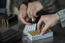 U.S. Air Force office of Special Investigations Special Agent Sam Lee, with Detachment 632, and Airman 1st Class Digiacinto, a 354th Security Forces Squadron response force member, prepare magazines for a small arms competition at Eielson Air Force Base, Alaska, May 17, 2016, as part of National Police Week activities. The small arms competition was one of the main events for the week, along with equipment displays, a military working dog competition and the Fallen Heroes 5K Run/Ruck. (U.S. Air Force photo by Staff Sgt. Joshua Turner/Released)
