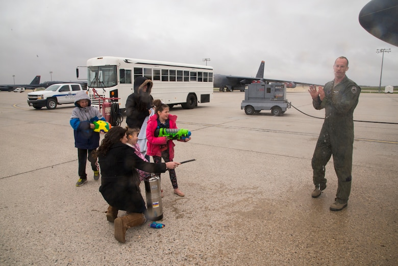 Maj. Michael Middents, 5th Bomb Wing director of staff, celebrates his fini-flight with his family on the flightline  at Minot Air Force Base, N.D., May 11, 2016. The fini-flight tradition began during World War II. (U.S. Air Force photo/Airman 1st Class Christian Sullivan)